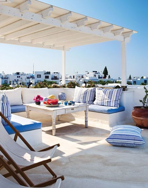 a sea Mediterranean terrace with all wihte everything and blue and striped textiles and bold tableware