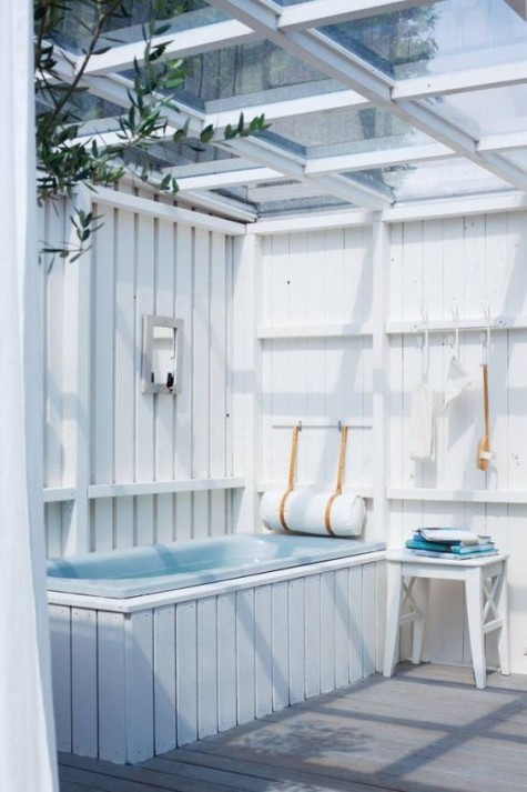 a sea-inspired all-white outdoor bathroom with a glazed ceiling, a blue tub and a wooden stool