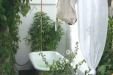 a simple rustic outdoor bathroom with potted greenery and blooms, a vintage tub on a wooden deck and walls and curtains for privacy