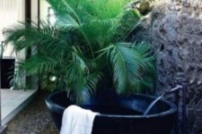 a simple yet gorgeous outdoor oasis with a potted palm, a black stone tub and pebbles on the ground