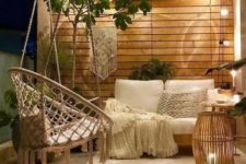 a small contemporary meets boho terrace with lights, macrame, candles and greenery plus enough light