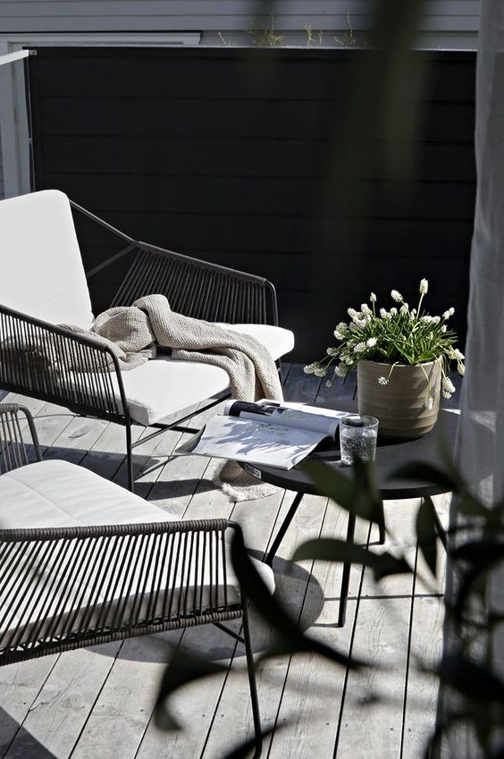 a small modern terrace with metal and wicker chairs, a blakc table, some simple blooms in a pot and a weathered deck