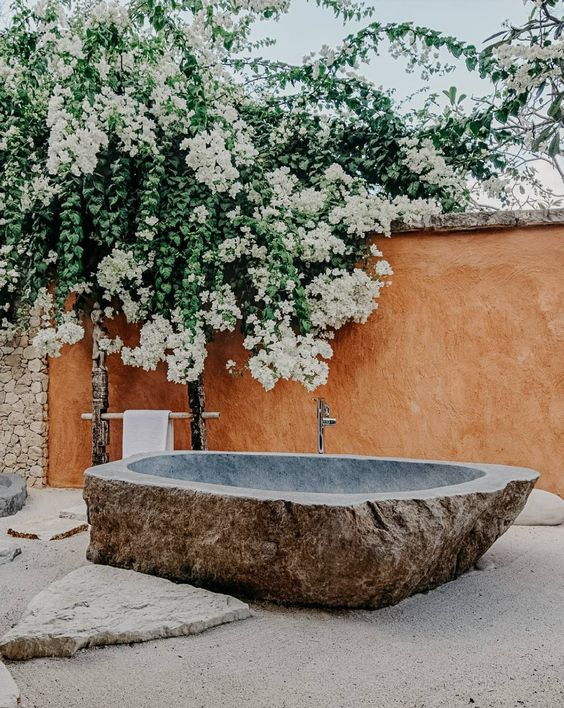 a stunning outdoor bathroom with a carved stone tub placed on sand, rocks and lush blooms over the tub