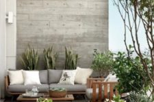 a stylish contemporary terrace with wooden furniture, greys and off-whites, potted greenery and plants