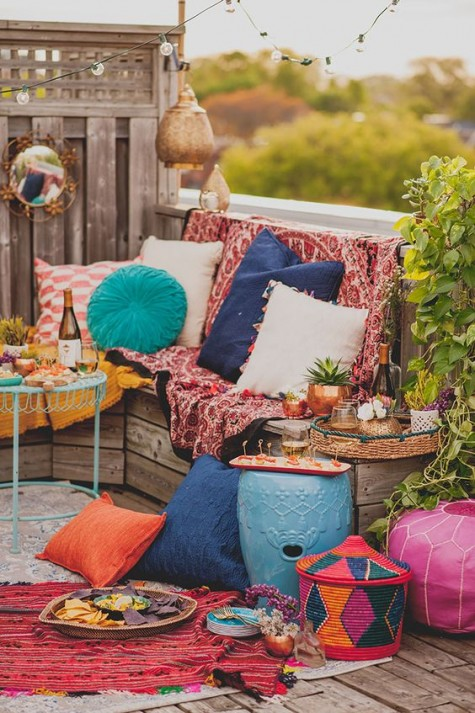 a super colorful boho chic terrace with a wooden bench, colorful pillows and textiles plus some fabric baskets