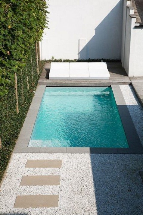 a super minimalist and stylish outdoor space with a wooden deck, gravel, a large white lounge and a plunge pool clad with tiles