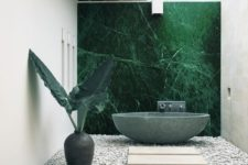 a super stylish minimalist outdoor bathroom with a green marble statement wall and a matching oval tub, tropical leaves and pebbles and tiles