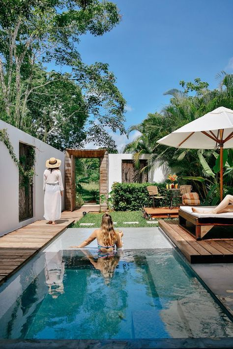 a tropical backyard with a plunge pool, decks, wooden and wicker furniture and lots of greenery around