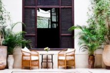 a tropical backyard with rattan chairs, a dark wooden screen, a plunge pool and potted greenery all aroud
