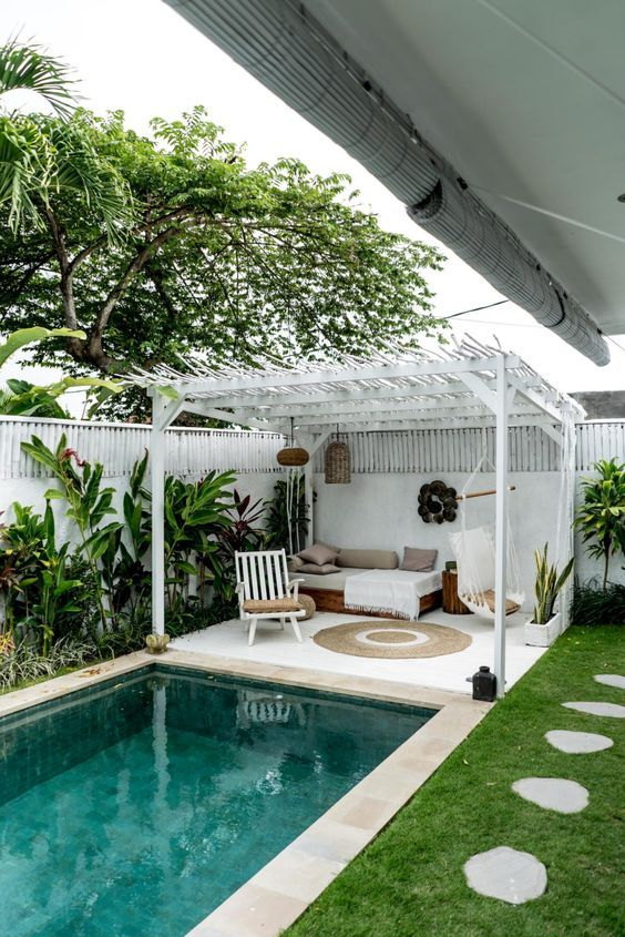 a tropical boho backyard with a plunge pool, greenery along the wall and a white cabana with some boho furniture