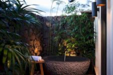 a tropical outdoor bathroom with stone walls around and a stone floor, greenery growing and some lights