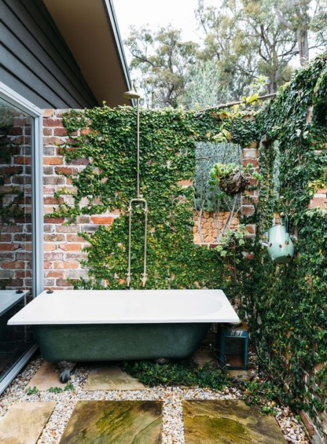 a vintage industrial outdoor bathroom with a brick wall covered with vines and a green bathtub