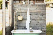 a weathered wood wall with hooks from one side and a low wall on another to keep some privacy