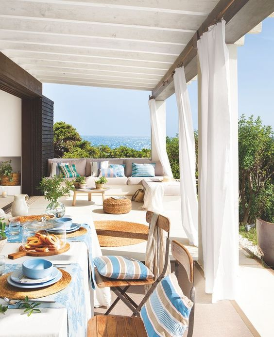 a welcoming Mediterranean terrace with neutral furniture, bright striped textiles, potted greenery and wicker and jute