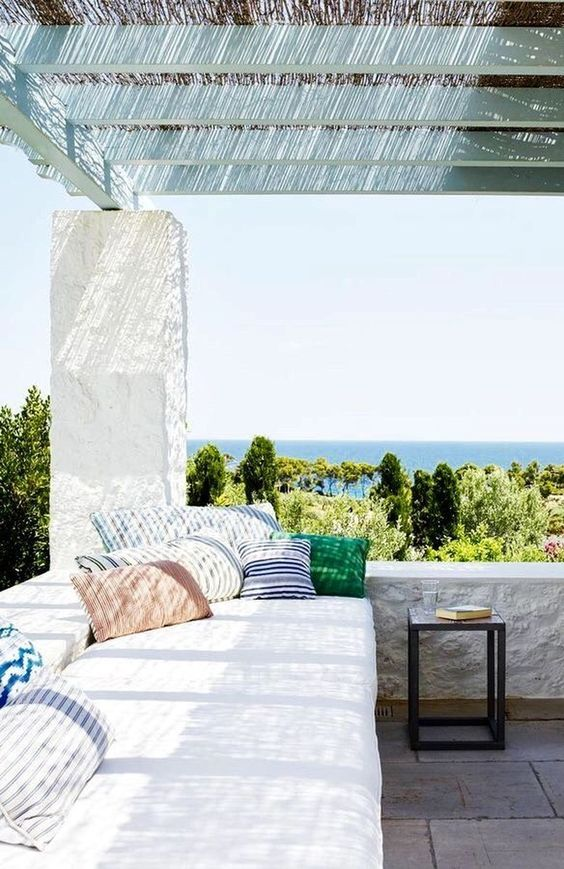 a welcoming Mediterranean terrace with white plaster, a large daybed with bright throws and a table