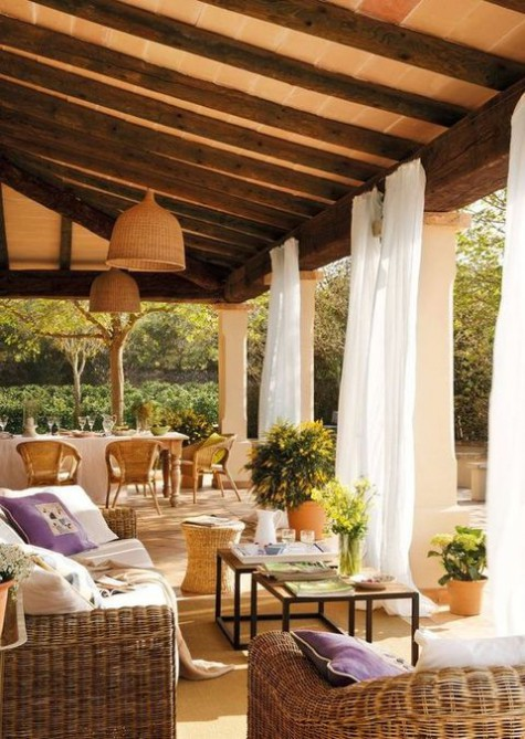 a welcoming Mediterranean terrace with wicker furniture and lampshades, potted greenery, white curtains to hide from the sun