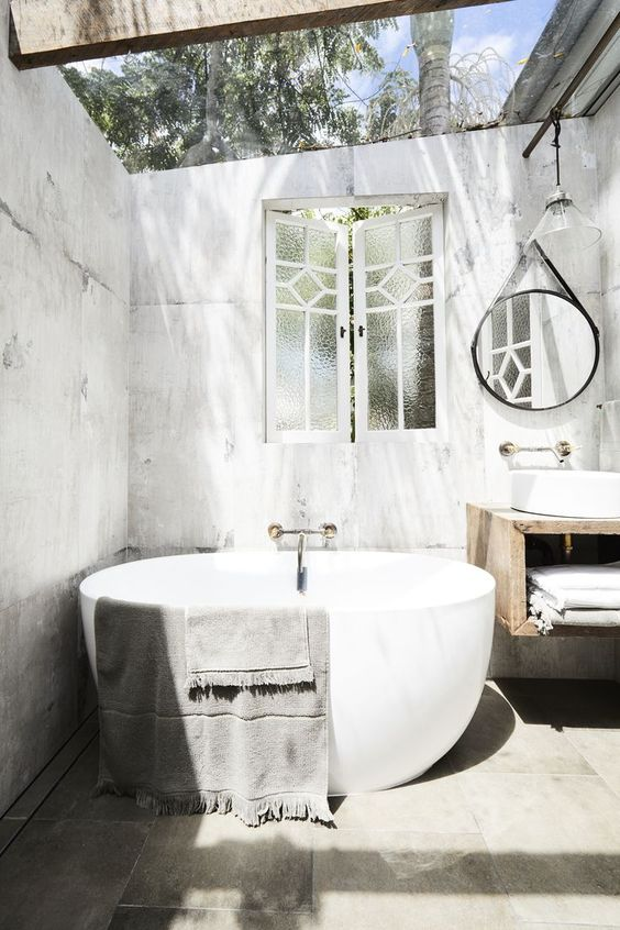 an industrial meets contemproary outdoor bathroom with an oval tub, a round mirror and a vanity with a sink