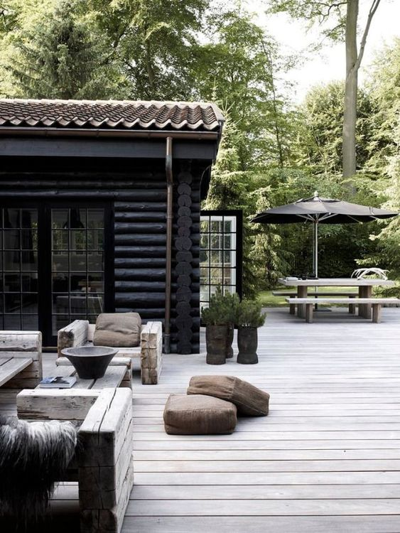 an outdoor Nordic space with wood beam furniture, potted greenery and leather floor cushions