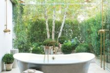 an outdoor bathroom placed in a private courtyard with greenery walls, potted greenery and a vintage tub