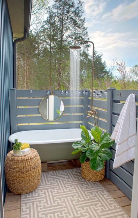 an outdoor bathtub plus a shower, wicker planters and a table and powder blue wooden plank screens all around for privacy
