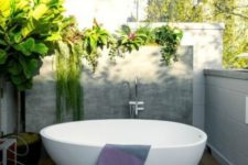 an outdoor deck with half walls all round to keep privacy yet get enough light, a stylish oval bathtub and lots of greenery