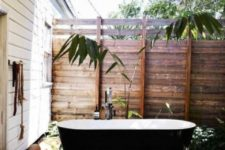 reclaimed wood privacy screens from all the sides, a black and white tub and some greenery growing here