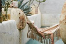 02 a boho chic pool space with much stone, cacti and trees growing around, a boho tassel hammock over the pool