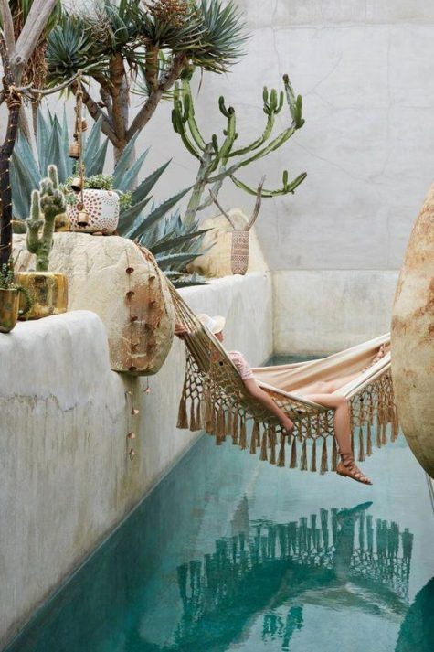 a boho chic pool space with much stone, cacti and trees growing around, a boho tassel hammock over the pool