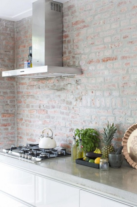 a modern white kitchen with a whitewashed red brick wall, not just a backsplash for a textural touch
