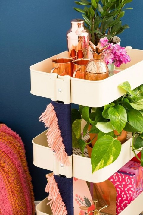a simple IKEA Raskog hack with colorful yarn for a boho feel is a cool mobile bar that will fit a boho space