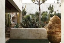 03 a boho pool space with a small pool with mosaic decor on the bottom, sculptures, growing cacti and trees