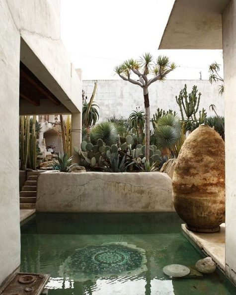 a boho pool space with a small pool with mosaic decor on the bottom, sculptures, growing cacti and trees