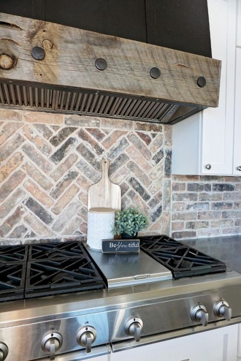 a neutral brick backsplash clad in a herringbone pattern, a weathered wood hood and a metal cooker to add boldness to the space