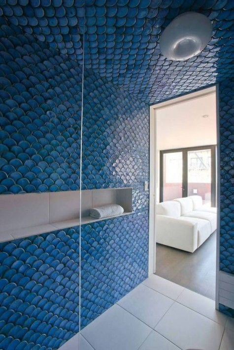 a shower space completely covered with blue fishscale tiles looks really mermaid-like and bold, your shower will stand out with such tiles for sure