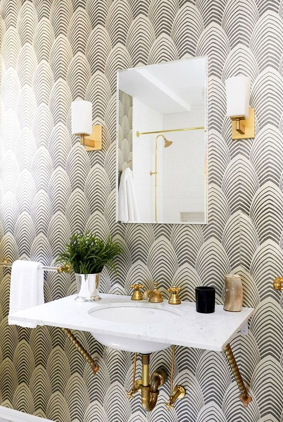 art deco wallpaper and brass touches make the bathroom super chic and refined