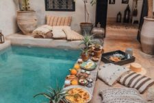 04 a boho pool space with potted greenery and cacti, lanterns, Moroccan blanket-inspired pillows and a pool covered with concrete