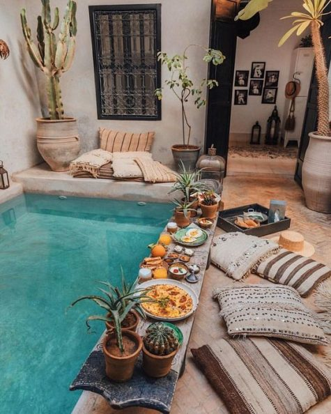 a boho pool space with potted greenery and cacti, lanterns, Moroccan blanket inspired pillows and a pool covered with concrete