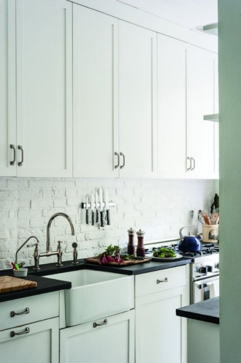 an all white kitchen with a white brick backsplash for a textural feel, black countertops and dark metal handles