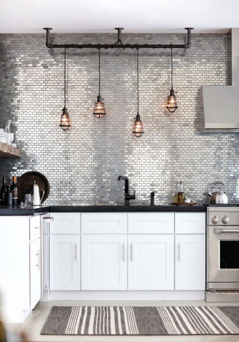 shiny silver tiles glam up the space and echo with stainless steel appliances