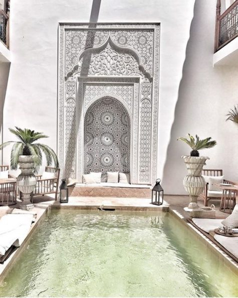 a bright Moroccan boho patio with amazing mosaic tiles, candle lanterns, rattan furniture, potted plants and neutral textiles
