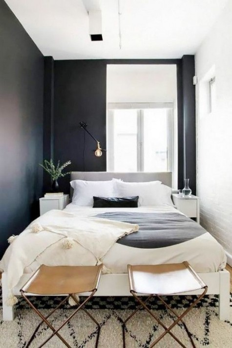 a tiny bedroom features only a large bed and very small nightstands plus leather stools for storage
