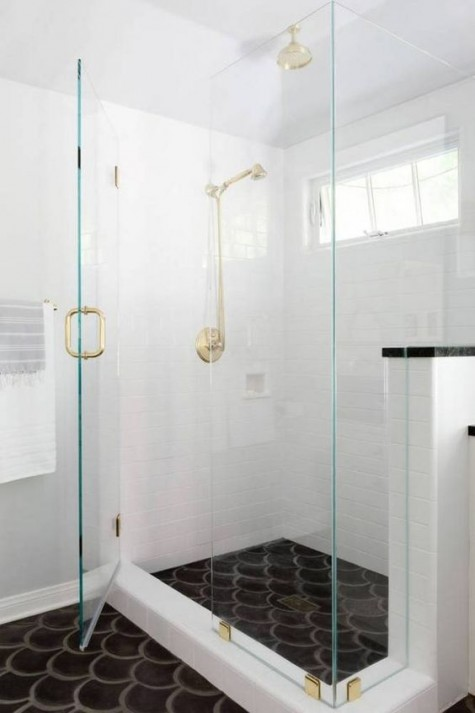 a white bathroom and a black fishscale tile floor for a bold monochromatic look accented with gold and brass