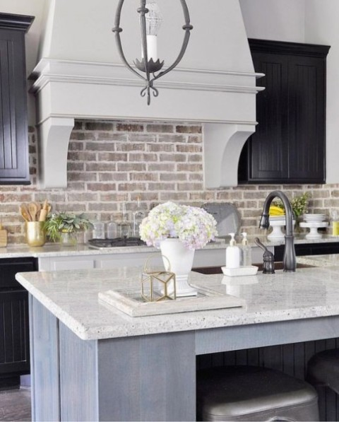 black cabinets, neutral stone countertops and a whitewashed brick backsplash plus an elegant neutral hood