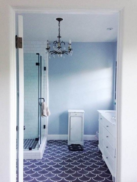 a blue and white bathroom with navy fishscale tiles on the floor, an elegant chandelier and white furniture looks sea-like