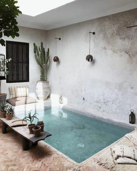a minimalist pool space with a boho feel, with a living edge bench, wall lamps, potted cacti, Moroccan inspired pillows