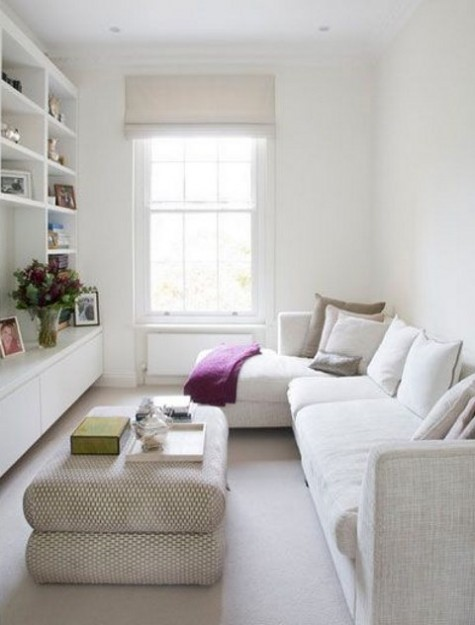 a tiny all neutral living room with a sectional sofa, a large ottoman and a built in shelving unit