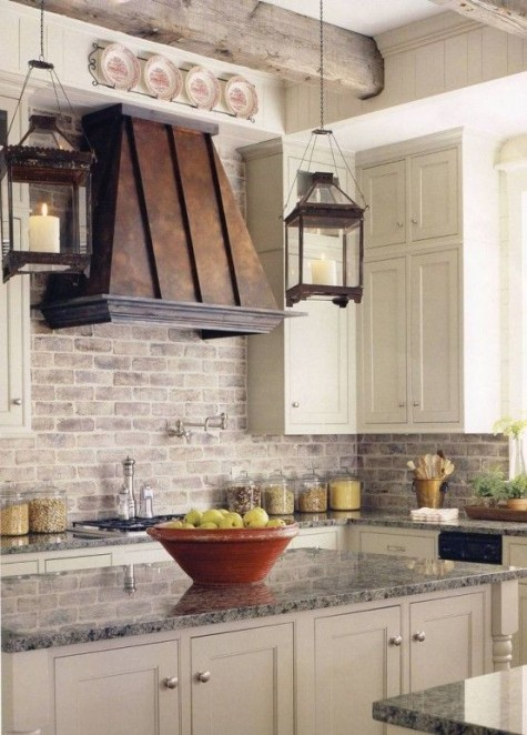 creamy cabinets, a dark metal hood, a whitewashed red brick backsplash for a bold farmhouse space
