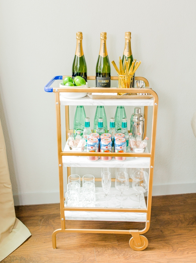a chic bar cart out of a usual IKEA utility cart repainted and decorated with contact paper is a great idea