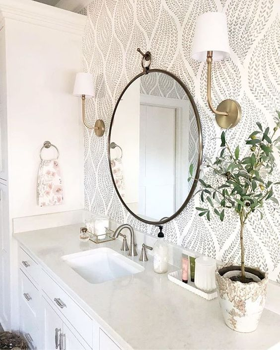 a chic farmhouse bathroom done in neutrals, with printed wallpaper, a stone countertop and touches of brass and gold