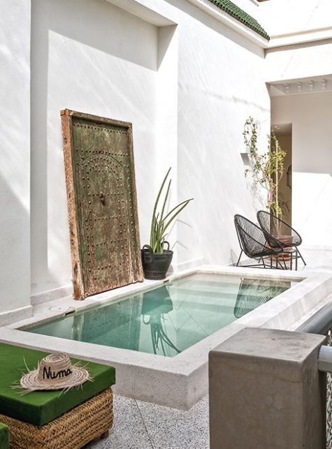 a minimalist pool space with boho touches, a wicker bench, an antique Asian door, metal chairs and potted plants